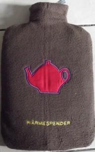 """Der Bezug aus Double Fleece in braun mit """"Teekanne""""-Applikation und der Aufschrift """"Wärmespender"""""""