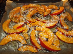 Kürbis auf dem Blech mit roten Zwiebeln und Parmesan